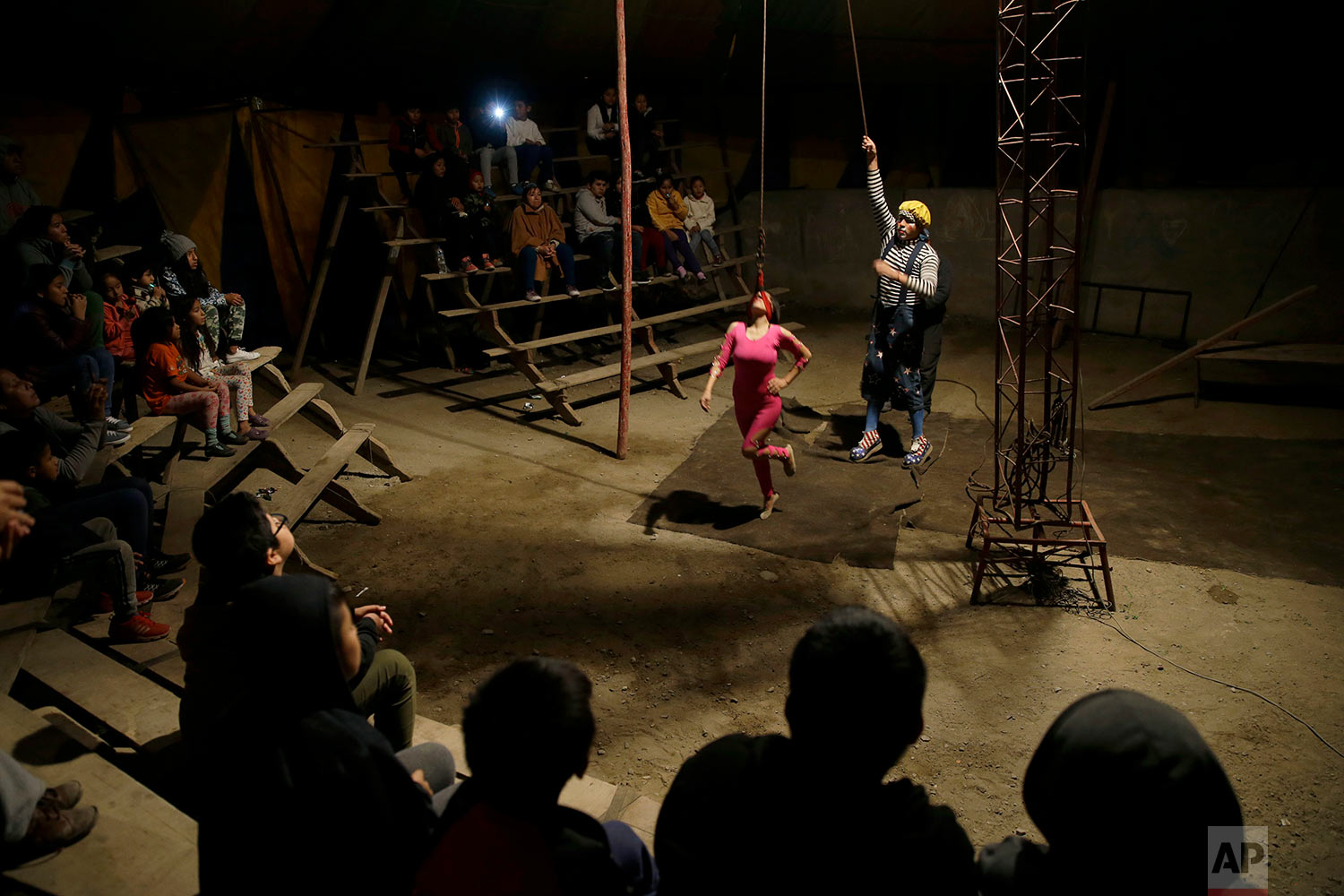 """""""Vaguito"""" the clown assists acrobat Brenda Aguila as she prepares to hang from her neck, as spectators watch the Tony Perejil circus, set up in the shanty town of Puente Piedra on the outskirts of Lima, Peru, July 8, 2018. The circus owner, Jose Alvarez, said he remembers happier times in the 1980s, when his father filled their circus tent with people even though Peru was in the midst of an economic crisis and a war raged between the state and Sendero Luminoso guerrillas. (AP Photo/Martin Mejia)"""