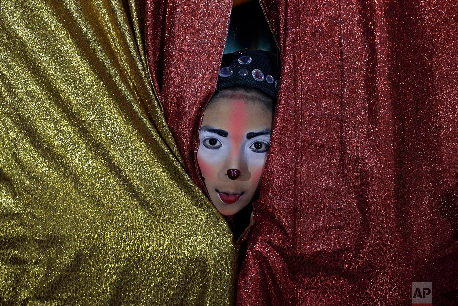 """Joshep Balta, who plays the part of a clown named """"Cachupito,"""" peers through the tent curtain to see how many people are waiting for the show, put on by the International Circus, set up in the shanty town of Puente Piedra on the outskirts of Lima, Peru, July 20, 2018. Balta, a 12-year old clown whose parents work at the circus setting up and breaking down the encampment, was discovered by the circus two years ago when he was performing as a clown at street corners. (AP Photo/Martin Mejia)"""