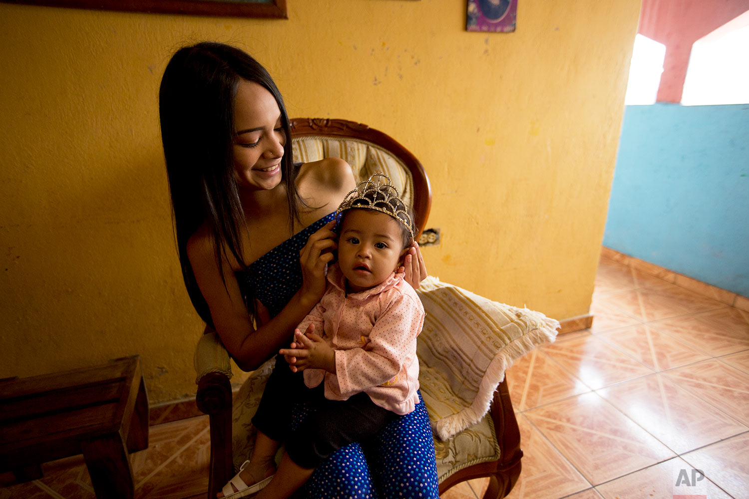 Johandrys Colls places a tiara on her niece Victoria at their home in a poor neighborhood on the outskirts of Caracas, Venezuela, July 1, 2018. Colls' parents have enrolled her in one of Venezuela's top modeling schools despite their modest income in hopes of transforming their daughter into a sought-after beauty queen. (AP Photo/Fernando Llano)