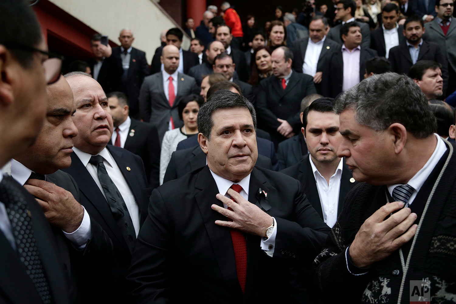 Paraguay's President Horacio Cartes straightens his tie as he waits for the arrival of the coffin of his Agriculture Minister Luis Gneiting, for a memorial service at the Colorado Party headquarters in Asuncion, Paraguay, July 27, 2018. The minister and three other people died when the twin-engine plane they were traveling in went down in a marshy area shortly after taking off at night from an airport. (AP Photo/Jorge Saenz)
