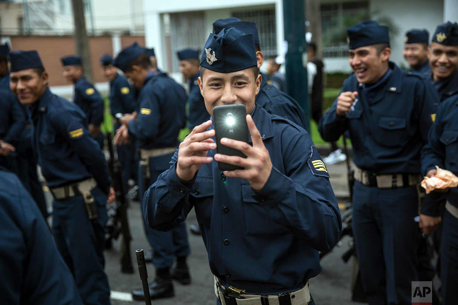 A soldier takes a cell phone picture of journalists before the start of a military parade, part of Independence Day celebrations in Lima, Peru, July 29, 2018. (AP Photo/Rodrigo Abd)