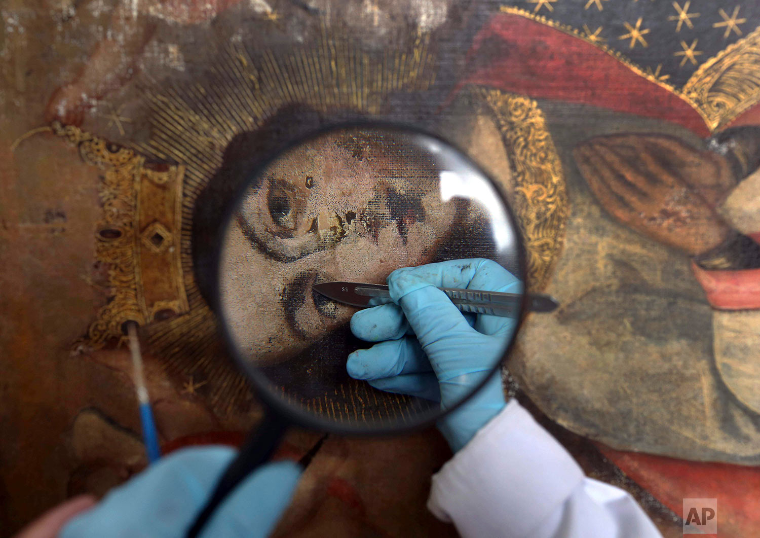 In this March 1, 2018 photo published in July, an art restorer works on a 17th century painting in a studio at the Ministry of Culture Restoration Center in Cuzco, Peru. The center receives calls for help from small churches in remote Andean villages that have existed for centuries, and many of the paintings have endured punishing rain, sun, mold, nibbling moths and even flawed repairs by untrained hands. (AP Photo/Martin Mejia)