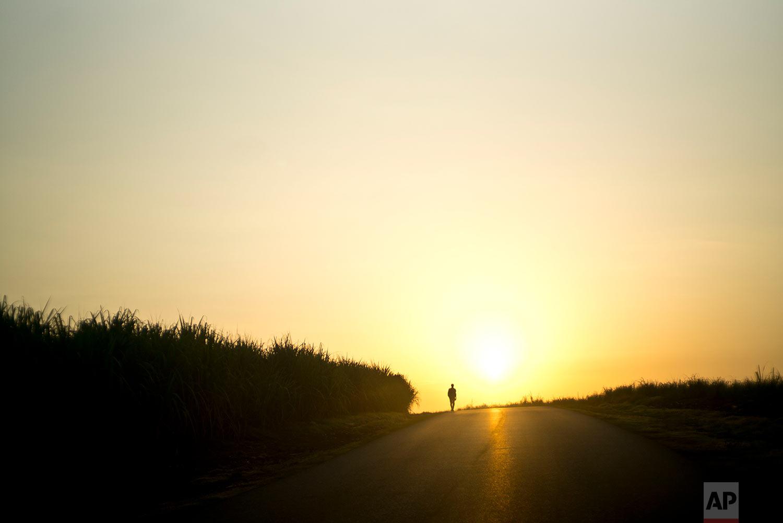 A man walks along a road at dawn, away from Guantanamo, Cuba, July 25, 2018.
