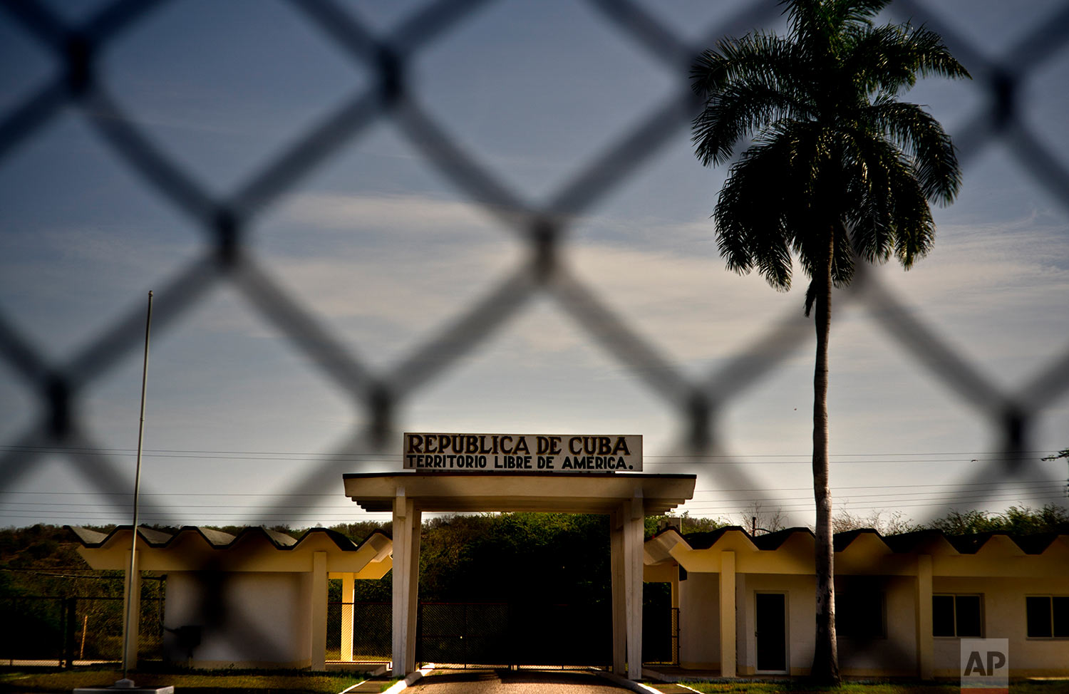 """A Cuban building carries the Spanish message """"Republic of Cuba. Free American Territory,"""" behind a gate marking the border with the naval base at Guantanamo Bay, June 6, 2018"""