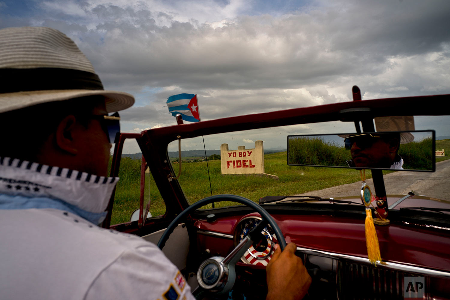 """A taxi driver steers his classic American car past a sign that reads in Spanish """"I'm Fidel"""" on the road to Guantanamo, Cuba,July 24, 2018."""