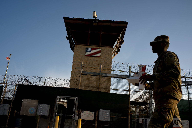 A U.S. soldier carries food past Camp VI at the naval base at Guantanamo Bay, June 5, 2018.
