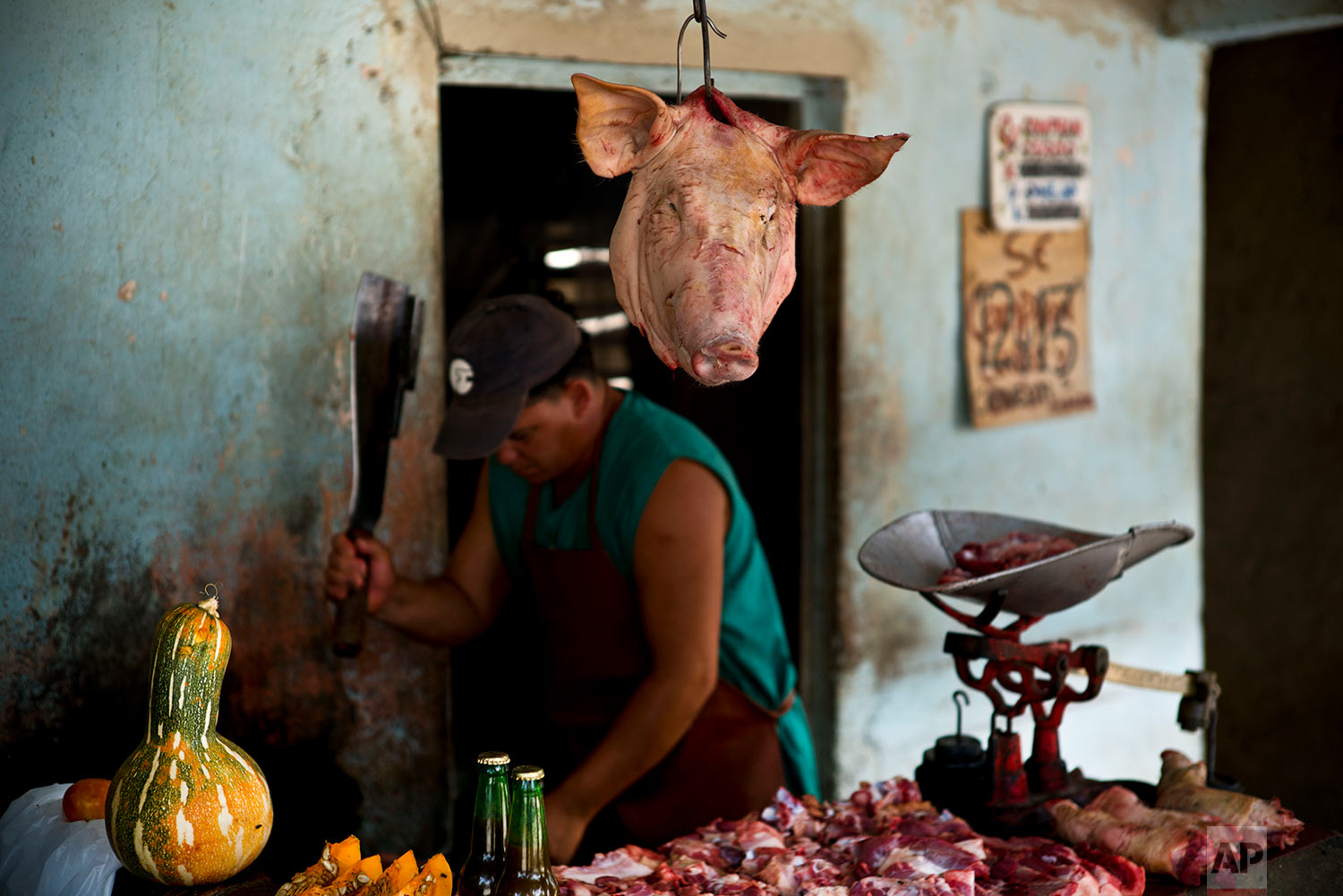 """A butcher works in Guantanamo, Cuba, July 25, 2018. Pork is the most accessible meat in Cuba, where the pig has its own song: """"El Puerco Mamifero Nacional,"""" or National Mammal Pork,"""" sung by the Buena Fe band."""