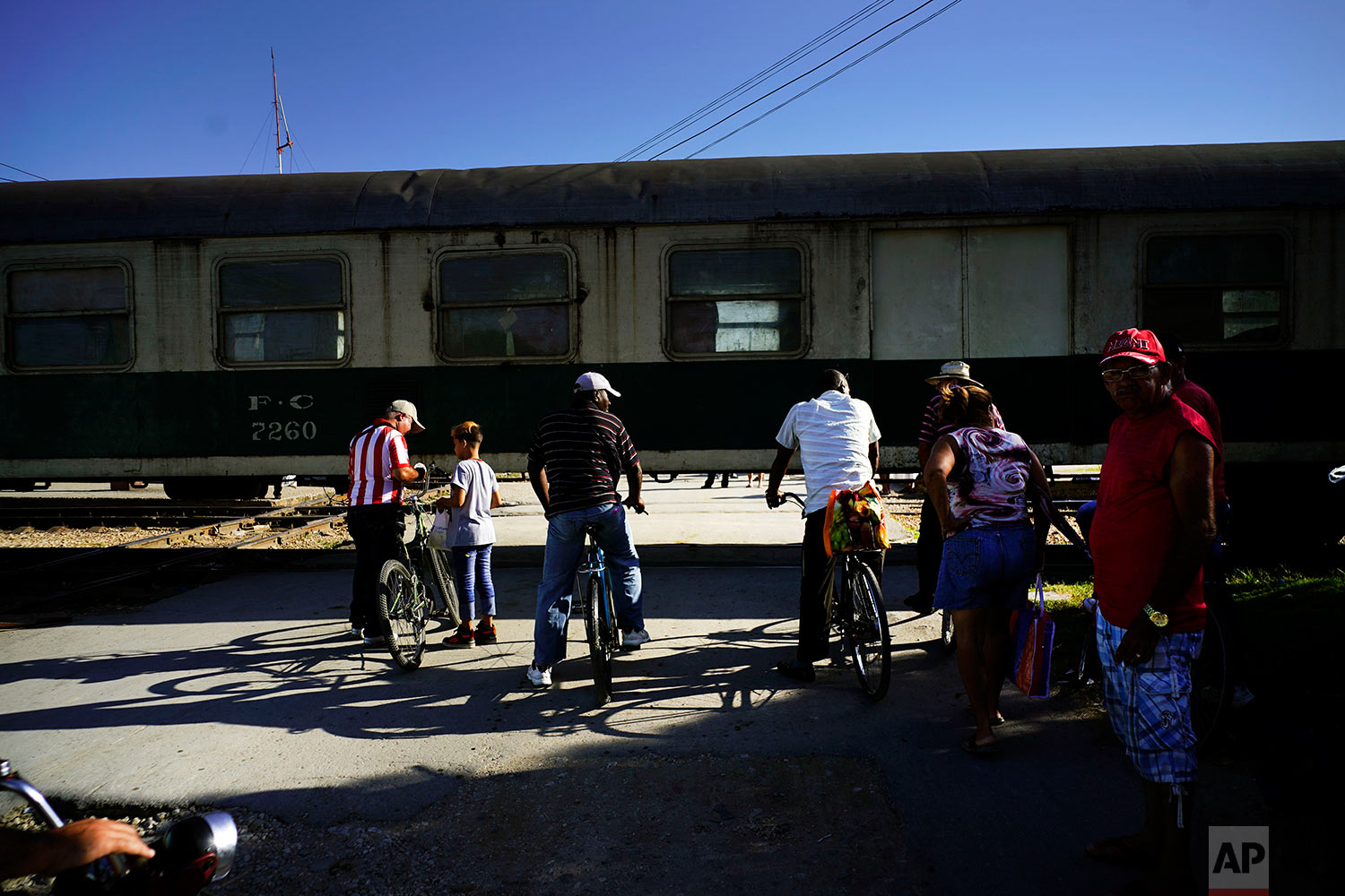 """Cubans wait for the """"El Guantanamero"""" train to move so they can cross the track in Guantanamo, Cuba,July 25, 2018."""