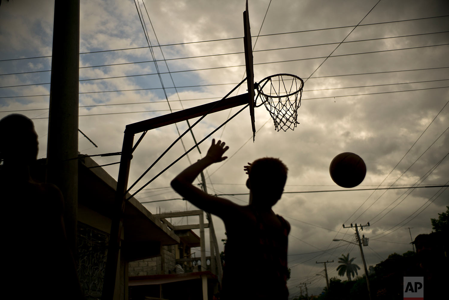 A youth plays basketball in Guantanamo, Cuba, July 24, 2018. Boys on summer break from school often meet at parks for a game of hoops.