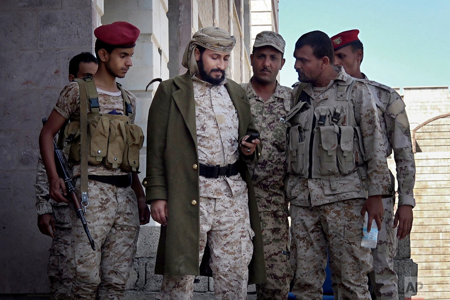 Adnan Rouzek, center, stands with fighters in Taiz. (AP Photo)