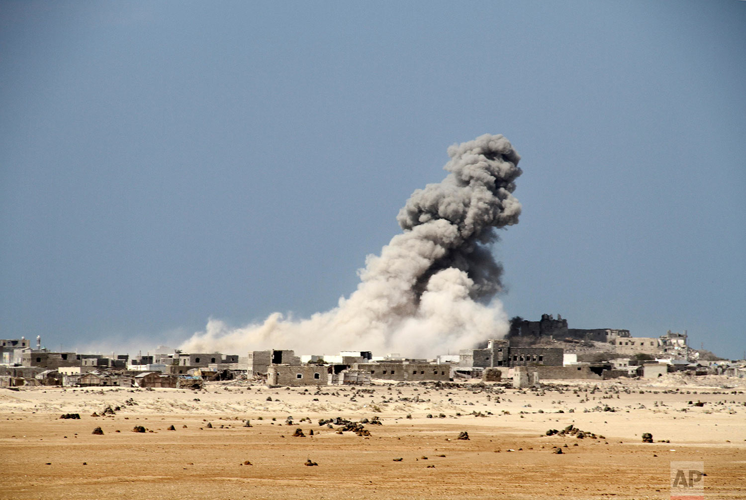 An explosion raises a cloud as coalition-backed fighters advance on the Red Sea port town of Mocha. (AP Photo)