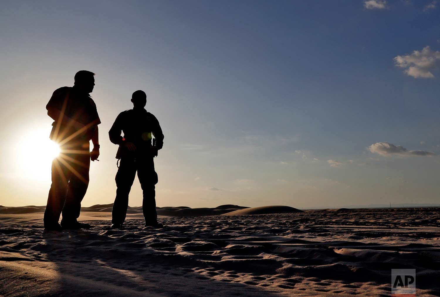 A pair of U.S. Customs and Border Patrol agents look at tracks in the sand along the floating fence that makes up the international border with Mexico, Wednesday, July 18, 2018 in Imperial County, Calif. (AP Photo/Matt York)