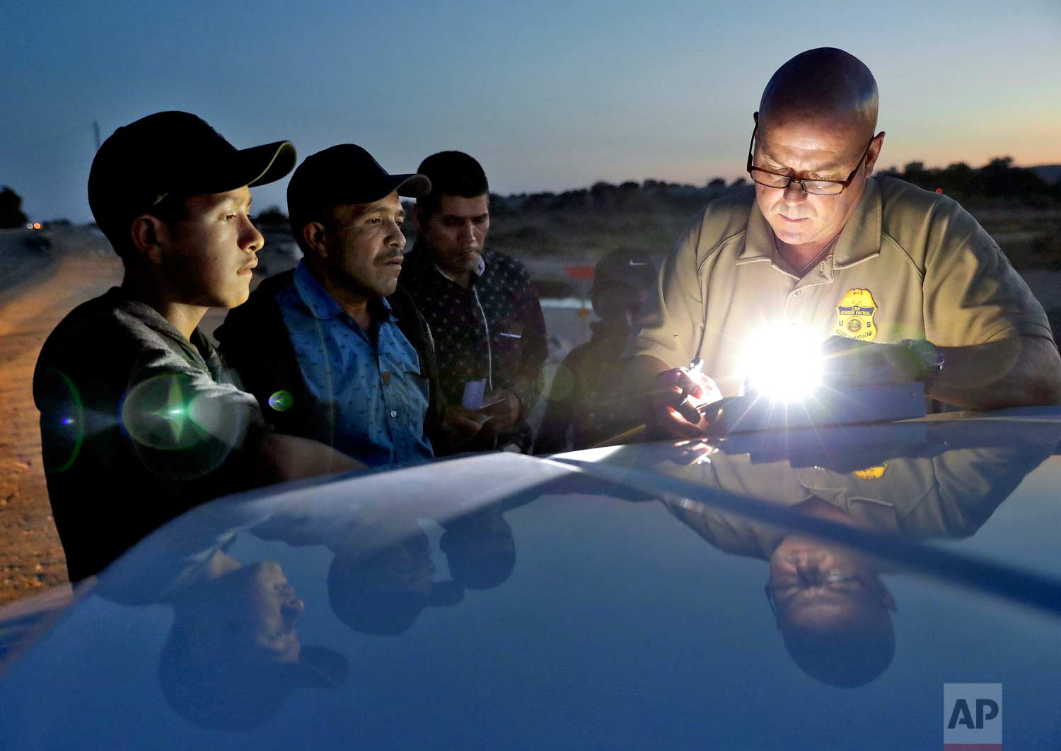 A U.S. Customs and Border Patrol agent gathers information on four Guatemalan nationals, including two men and a pair of 12 and 13-year-old boys, Wednesday, July 18, 2018, in Yuma, Ariz. (AP Photo/Matt York)