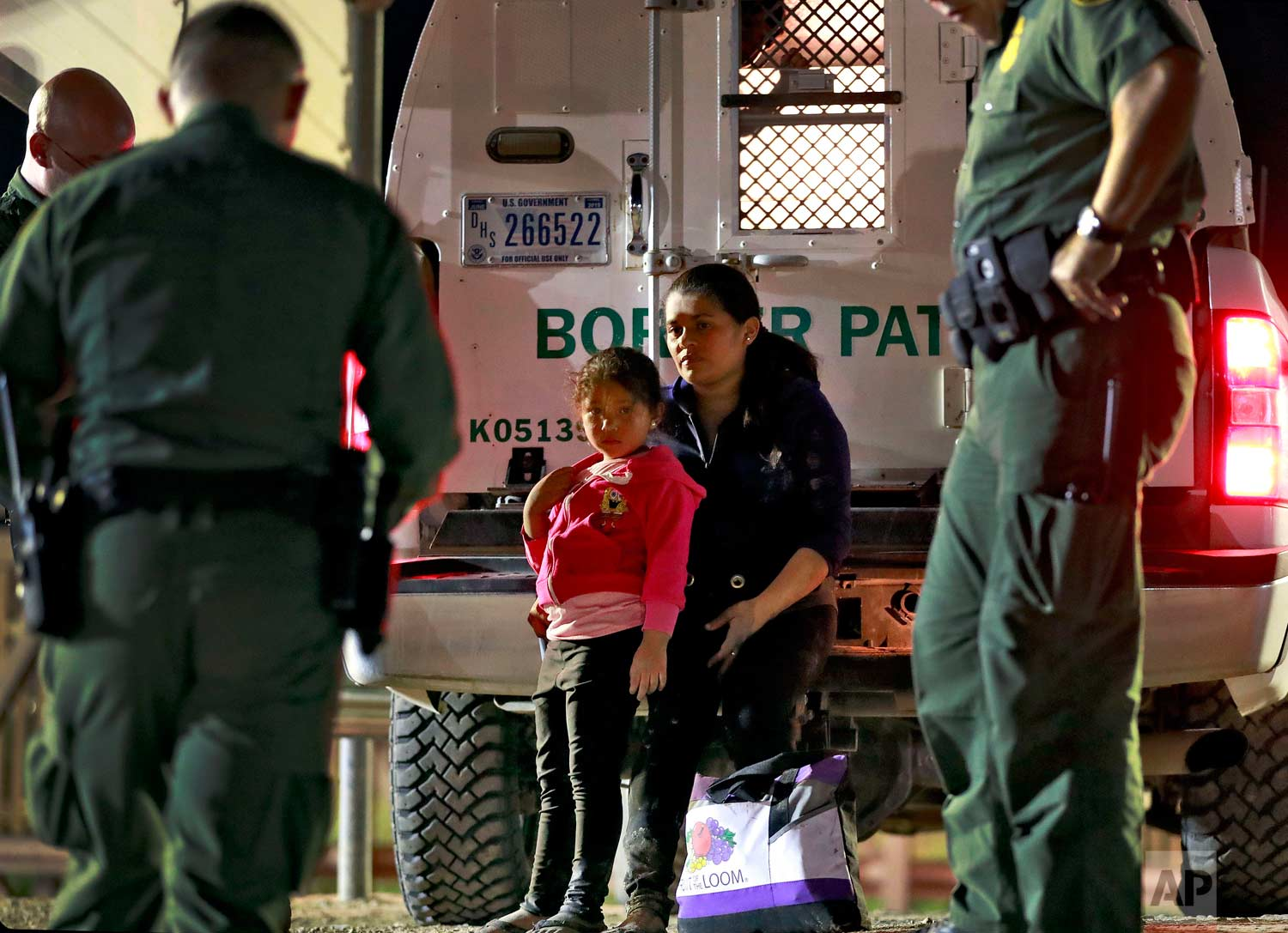 A mother and 5-year-old daughter from Honduras are detained by U.S. Customs and Border Patrol agents Wednesday, July 18, 2018, in San Luis, Ariz. (AP Photo/Matt York)