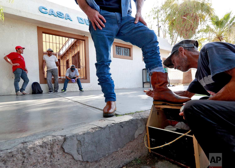 "Gonzalo Zavala, a Mexican national, has his boots shined outside the Asociacion Casa Del Migrante ""La Divina Providencia"" group house as three men stand outside, Thursday, July 19, 2018 in San Luis, Sonora, Mexico. (AP Photo/Matt York)"