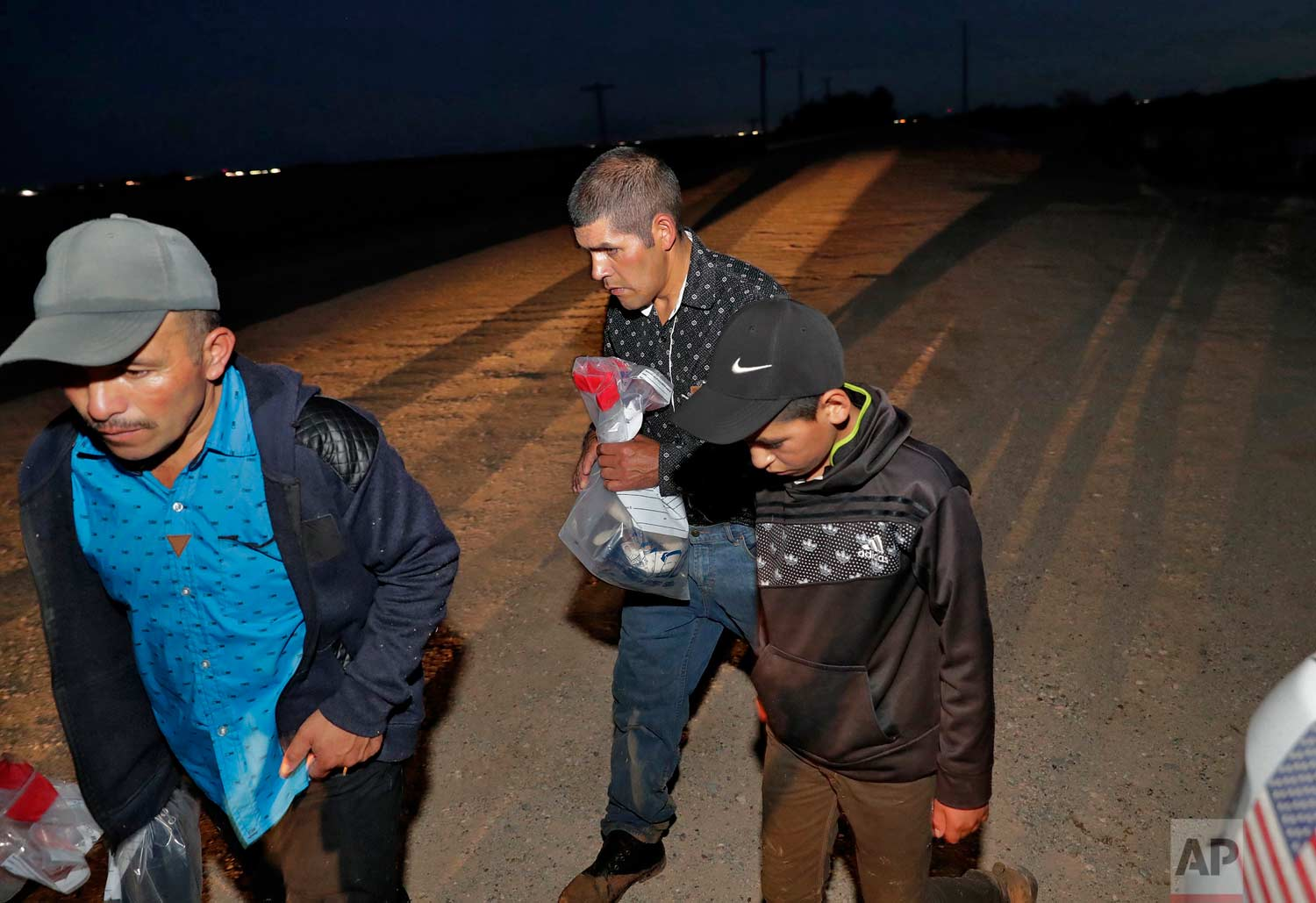 Three of four arrested Guatemalan nationals, two men and a 12-year-old boy, surrender to a U.S. Customs and Border Patrol agent, Wednesday, July 18, 2018 along the international border in Yuma, Ariz. (AP Photo/Matt York)