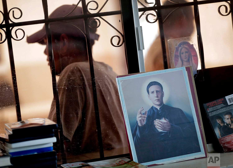 """Central American men are seen through a window behind religious imagery at the Asociacion Casa Del Migrante """"La Divina Providencia"""" group house Thursday, July 19, 2018 in San Luis, Sonora, Mexico. (AP Photo/Matt York)"""