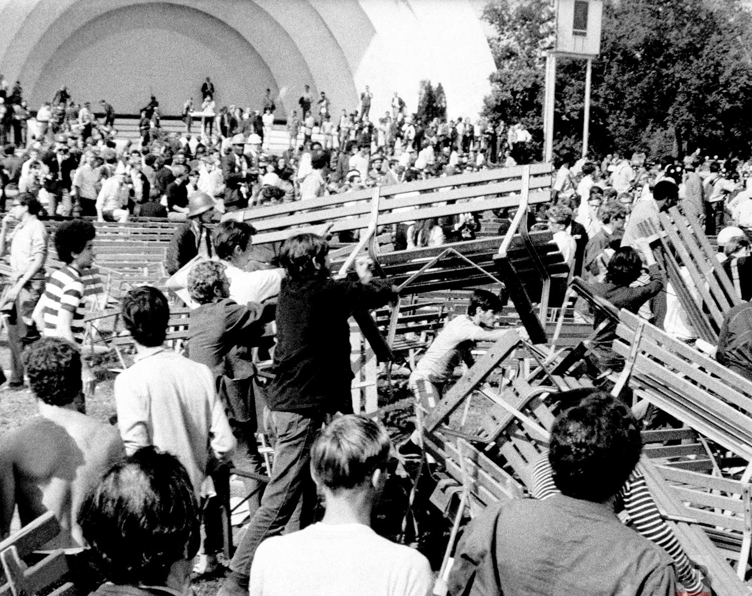 Long haired and bearded hippies and yippies use park benches at Grant Park's Band Shell to construct a barricade against Chicago police and National Guardsmen in Chicago on August 28, 1968. (AP Photo)