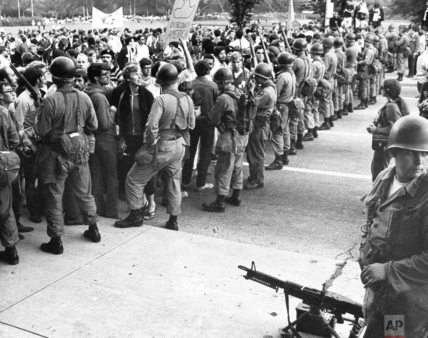 A National Guardsman stands beside a machine gun as others form a barrier against demonstrators in Chicago's Grant Park on August 28, 1968. (AP Photo)