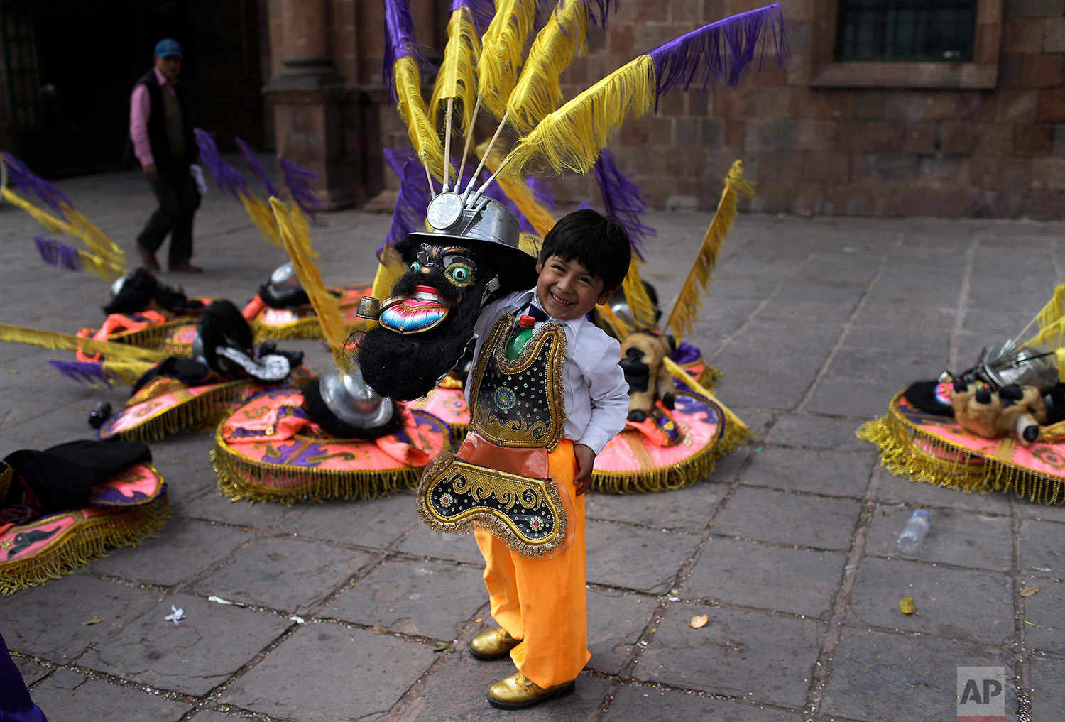 """Eight-year-old Miguel smiles while posing in his """"rey moreno"""" or """"black king"""" dance costume before the start of a procession honoring Our Lady of Copacabana, in Cuzco, Peru, Aug. 5, 2018. (AP Photo/Martin Mejia)"""