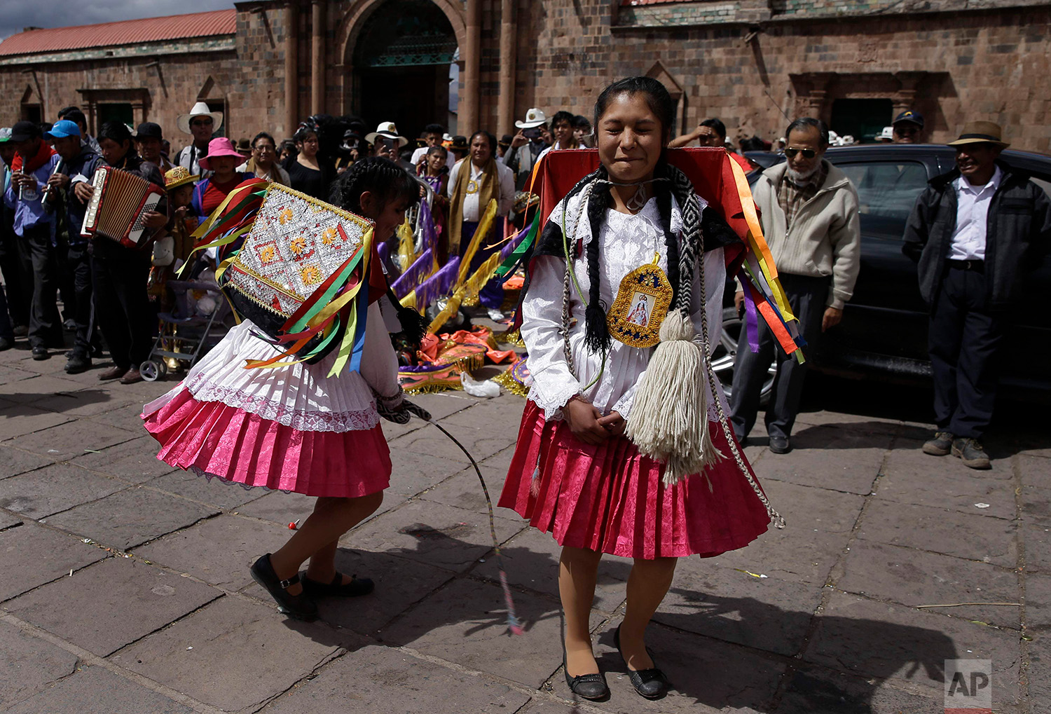 """A dancer winces in pain as she is whipped by a fellow dancer in an adaptation of the Inca warrior dance known as """"Kachampa"""", during celebrations honoring Our Lady of Copacabana, in Cuzco, Peru, Aug. 5, 2018. (AP Photo/Martin Mejia)"""