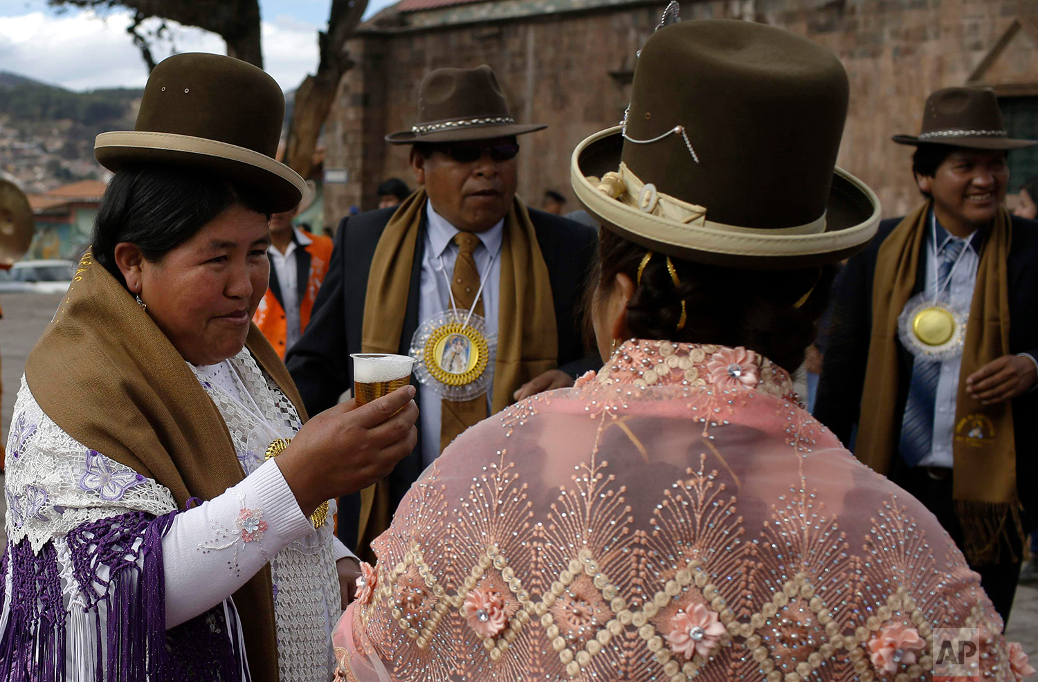 """""""Cholas"""" share a toast during a pause in the religious procession honoring Our Lady of Copacabana in Cuzco, Peru, Aug. 5, 2018. It is customary for organizers to offer free food and drink for celebrants. (AP Photo/Martin Mejia)"""
