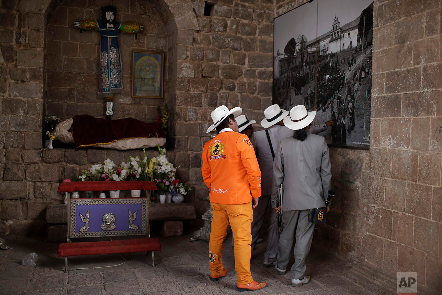 Members of the Majestic Union band look at a 1930's Martin Chambi photo, displayed on a facade of the Almudena Temple, in Cuzco, Peru. Aug. 5, 2018.  Chambi was known for photographing the elite members of Cuzco's society, as well as extensively documenting the Peruvian indigenous culture. (AP Photo/Martin Mejia)