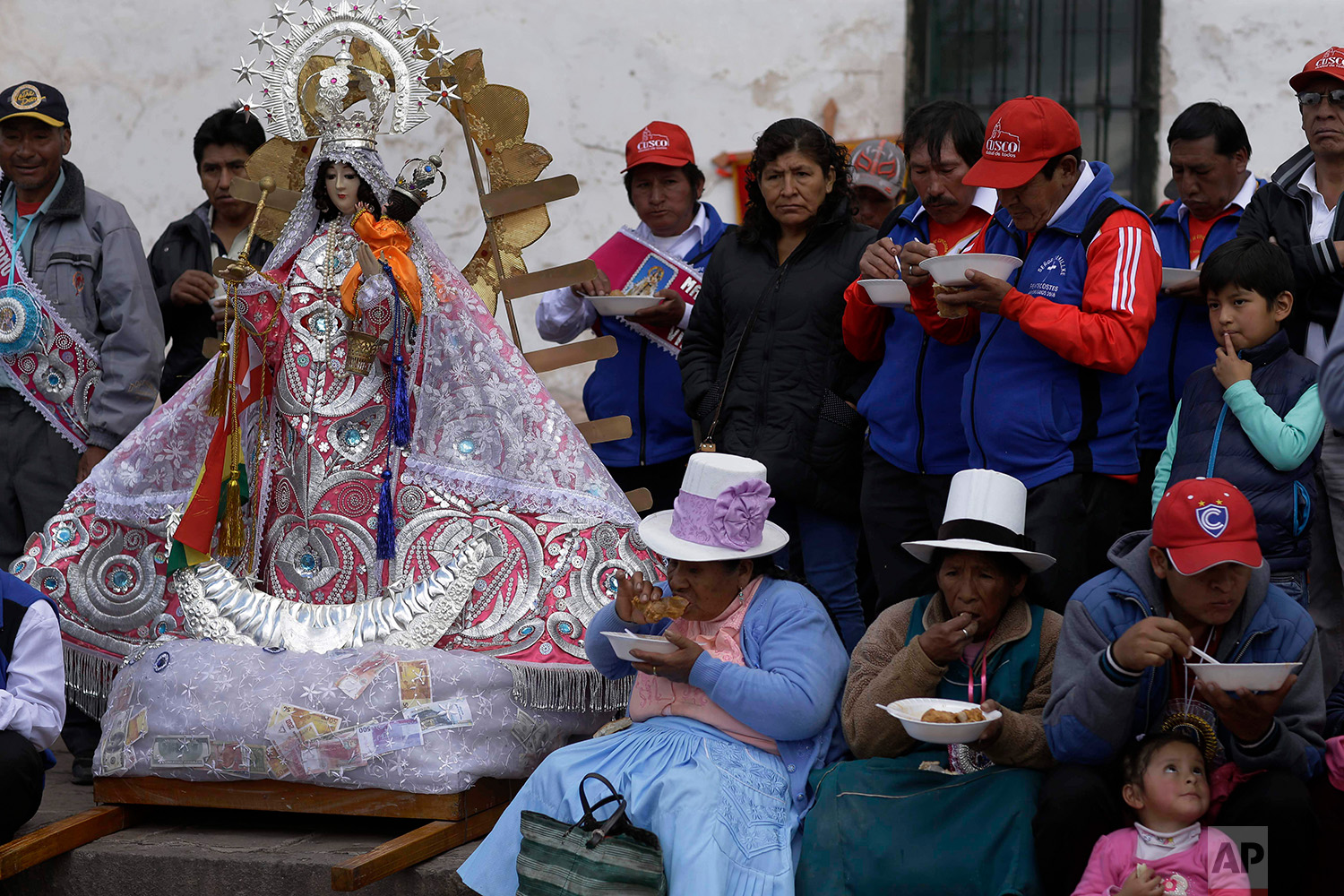 """""""Cargadores"""" or male carriers and devotees lunch on free bowls of beef and wheat soup during a pause in the religious procession honoring Our Lady of Copacabana, in Cuzco, Peru, Aug. 5, 2018. (AP Photo/Martin Mejia)"""