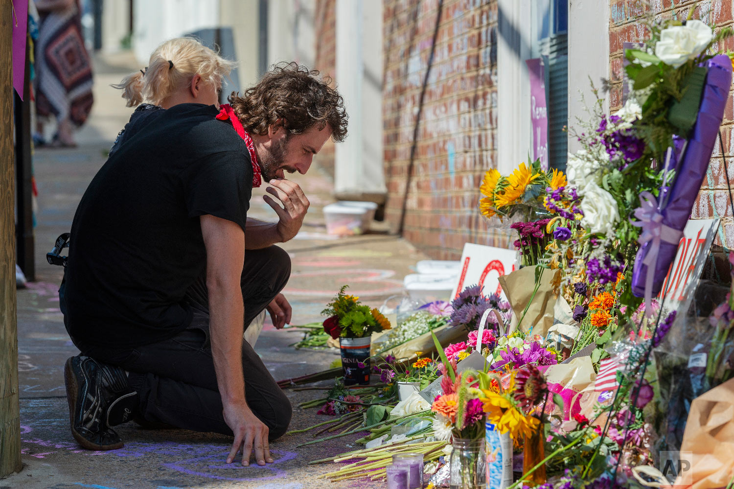 Charlie Spearman, foreground, and Jae Em Cafico kneel at a memorial dedicated to Heather Heyer who was killed during last year's Unite the Right rally, in Charlottesville, Va., Saturday, Aug. 11, 2018. The city of Charlottesville plans to mark Sunday's anniversary of a deadly gathering of white supremacists with a rally against racial hatred. (Craig Hudson/Charleston Gazette-Mail via AP)
