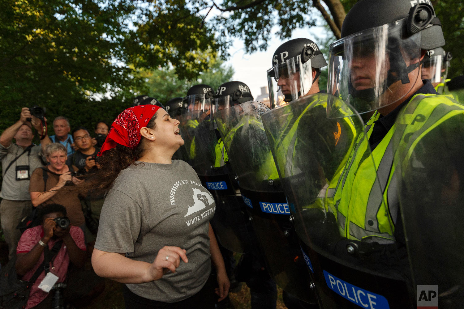 """Emily Filler attempts to dissuade state police from advancing on students rallying on the grounds of the University of Virginia on the anniversary of the """"Unite the Right"""" rally in Charlottesville, Va. Saturday, Aug. 11, 2018.  (Craig Hudson/Charleston Gazette-Mail via AP)"""