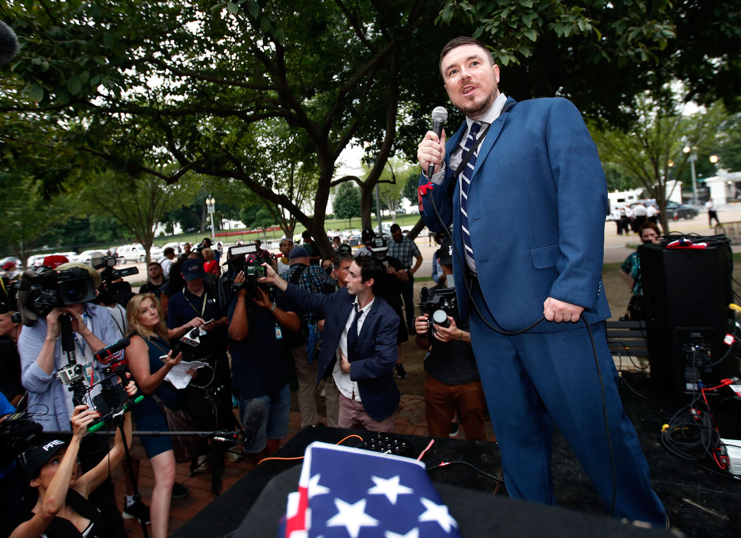 """White nationalist Jason Kessler talks during a rally near the White House on the one year anniversary of the Charlottesville """"Unite the Right"""" rally, Sunday, Aug. 12, 2018, in Washington. (AP Photo/Alex Brandon)"""