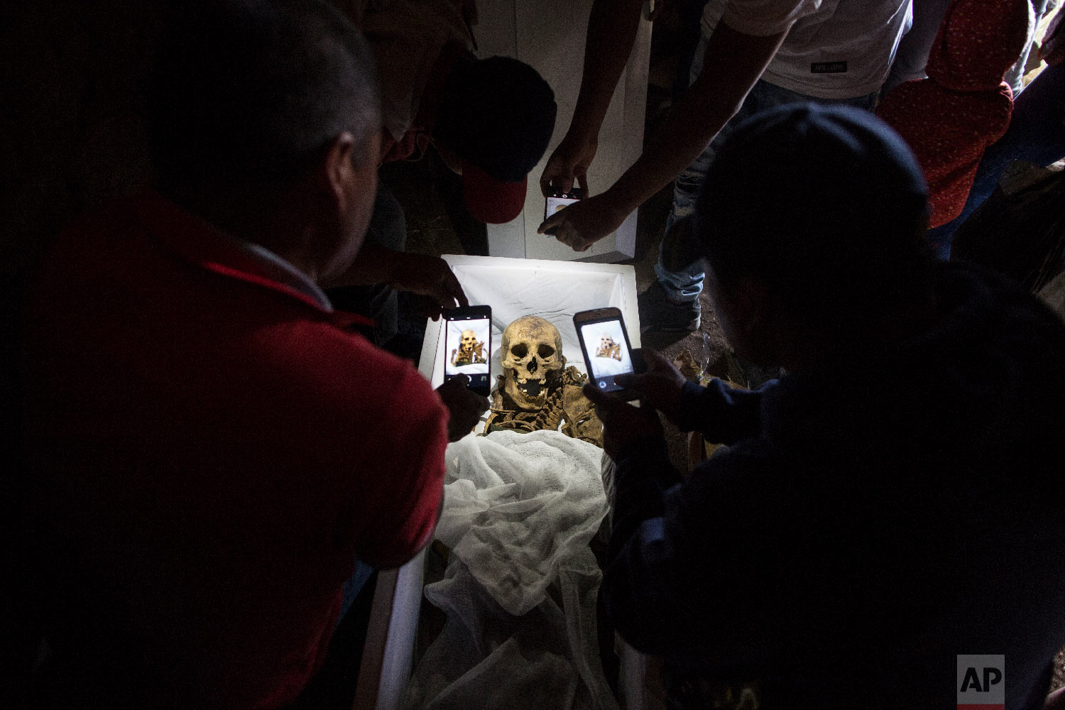 In this Aug. 14, 2018 photo, relatives take cell phone pictures of the remains of Fortunate Ventura Huamacusi, a man who was killed by the Peruvian army in 1983, before placing the coffin in its niche at the Rosaspata cemetery in Peru's Ayacucho province. (AP Photo/Rodrigo Abd)