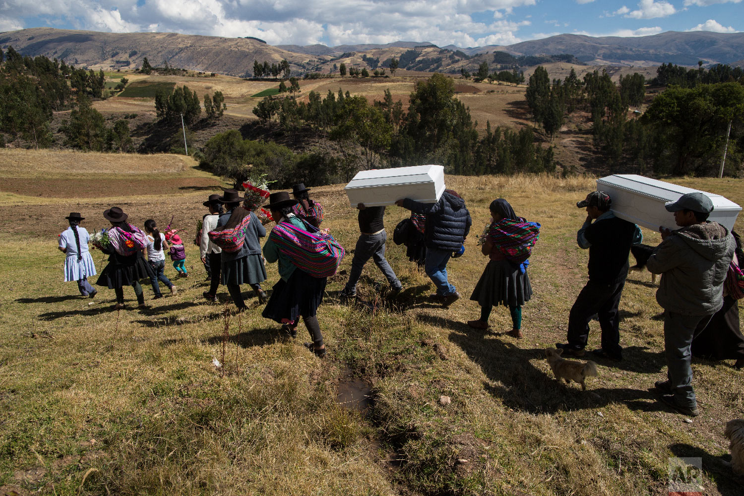 In this Aug. 15, 2018 photo, villagers carry the remains of people killed by the Shining Path guerrillas in 1984, during their proper burial in Tantana, in Peru's Ayacucho province. (AP Photo/Rodrigo Abd)