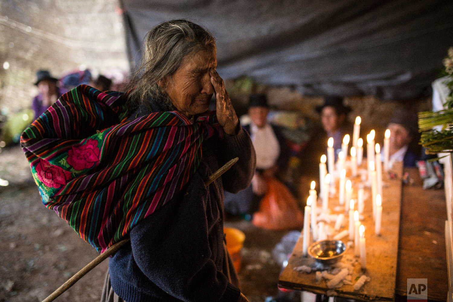 In this Aug. 15, 2018 photo, Paulina Tineo Canchari cries as she stands before the many coffins of relatives killed by the Shining Path guerrillas and the Peruvian army in the 1980s, during their proper burial in Quinuas, in Peru's Ayacucho province. (AP Photo/Rodrigo Abd)