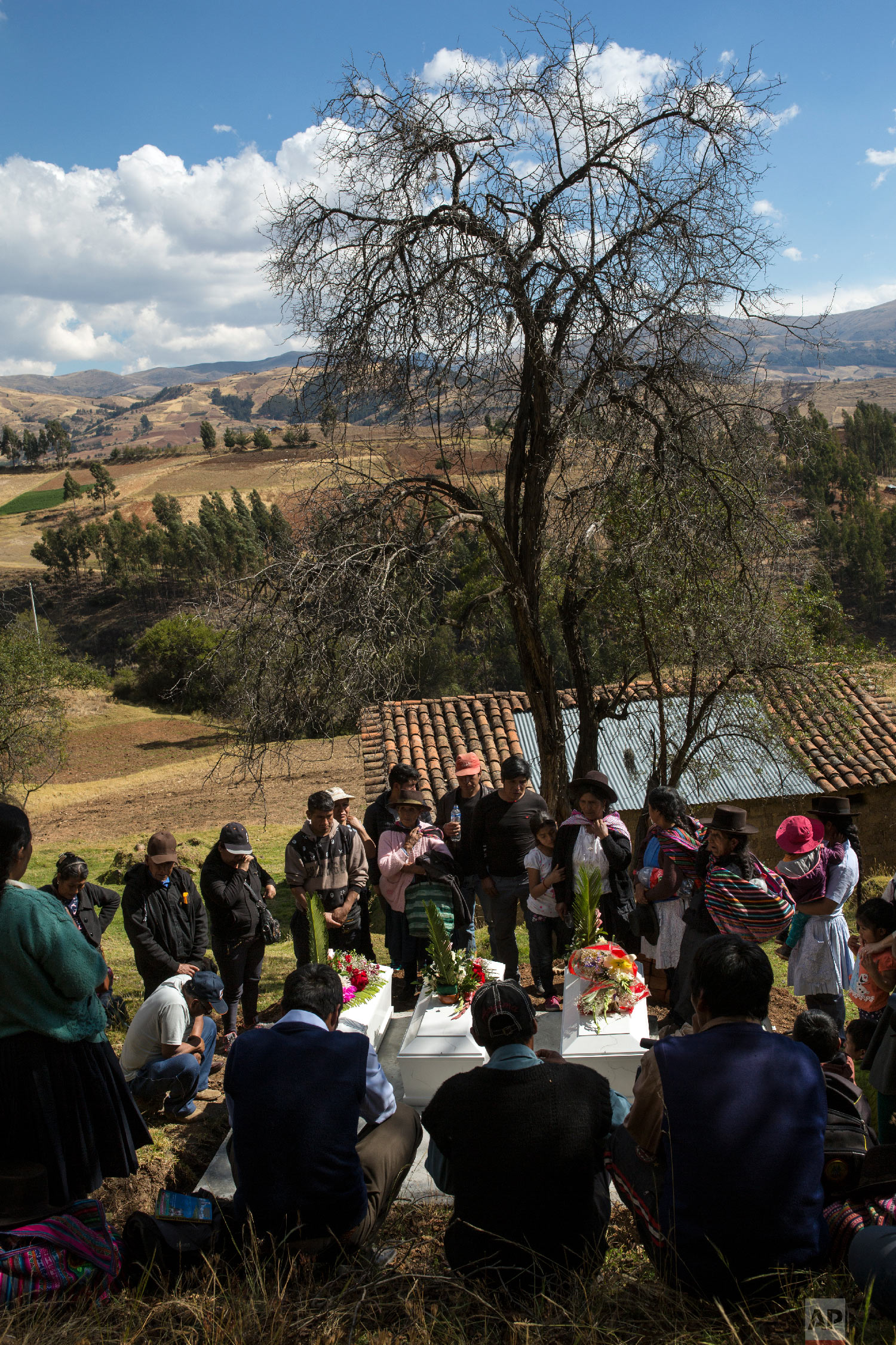 In this Aug. 15, 2018 photo, villagers gather around the coffins of their loved ones who were killed by Shining Path guerrillas in 1984, during their proper burial at the cemetery in Tantana, in Peru's Ayacucho province. (AP Photo/Rodrigo Abd)