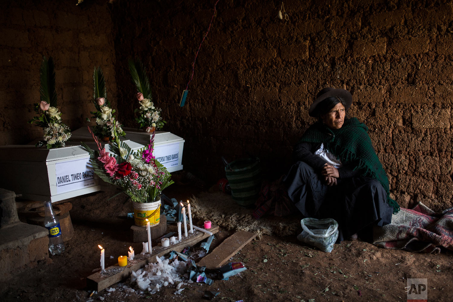 In this Aug. 15, 2018 photo, Marta Tineo Espinosa sits next to the coffins of her relatives who were killed by the Shining Path guerrillas and the Peruvian army in 1984, on the day of their proper burial in Tantana, in Peru's Ayacucho province. (AP Photo/Rodrigo Abd)