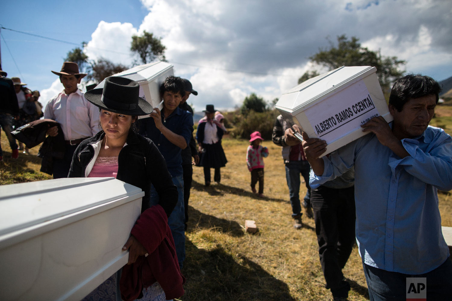 In this Aug. 15, 2018 photo, the relatives of people who were killed by the Shining Path guerrillas and the Peruvian army in the 1980s carry their remains to the cemetery for a proper burial in Quinuas, in Peru's Ayacucho province. (AP Photo/Rodrigo Abd)