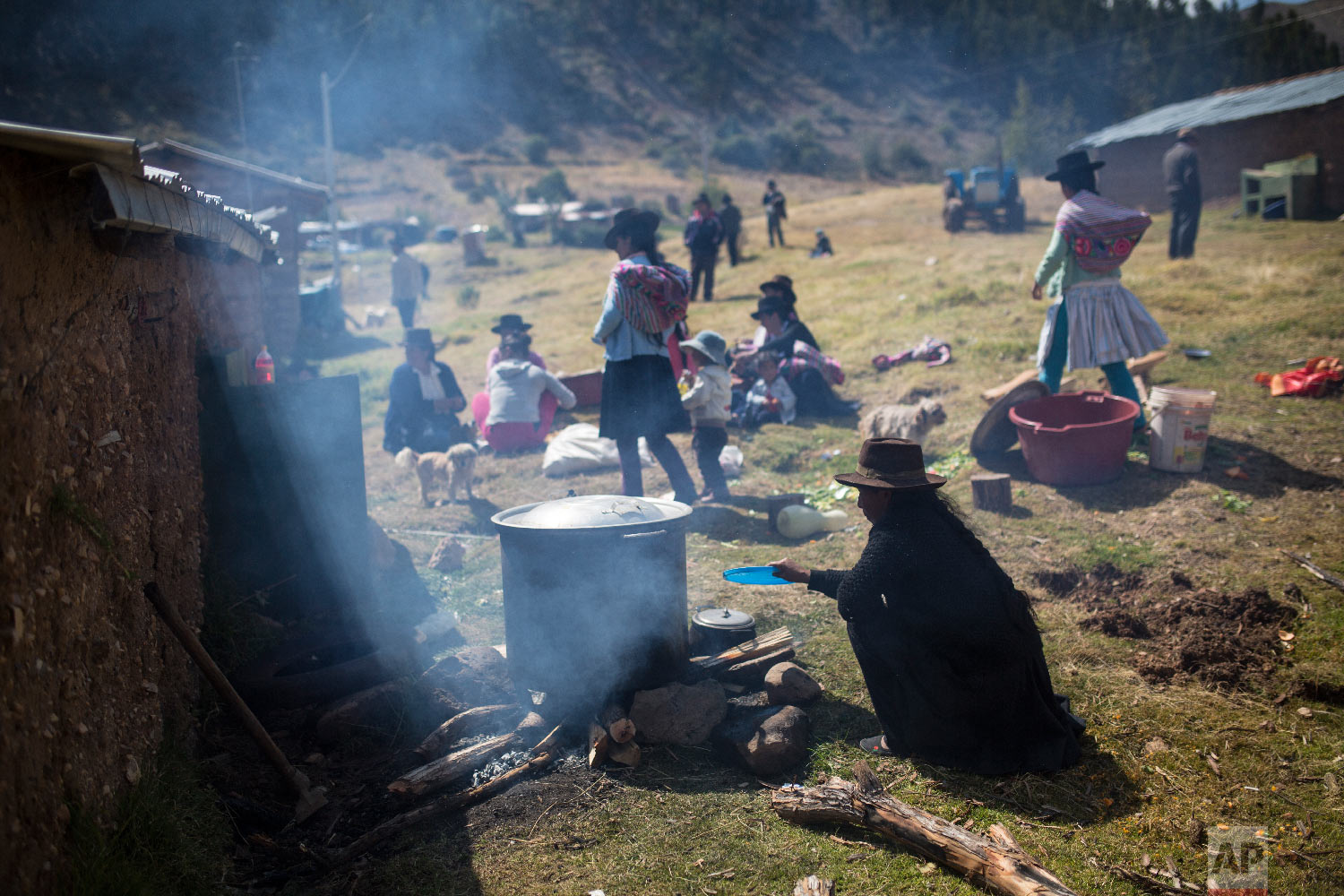 In this Aug. 15, 2018 photo, the relatives of villagers who were killed by the Shining Path guerrillas and the Peruvian army in the 1980s cook lunch after giving their loved ones a proper burial in Quinuas, in Peru's Ayacucho province. (AP Photo/Rodrigo Abd)