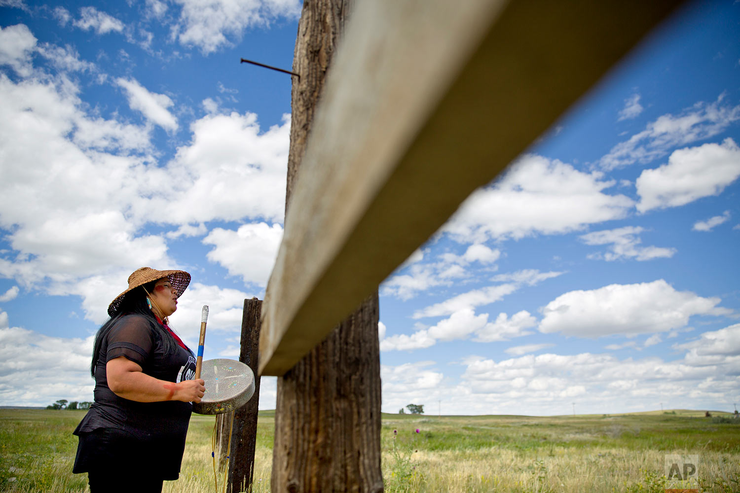 Roxanne White, whose aunt was murdered in 1996, sings and drums a women's warrior and honor song created for missing and murdered indigenous women, before joining a search in Valier, Mont., for Ashley HeavyRunner Loring,July 11, 2018. (AP Photo/David Goldman)