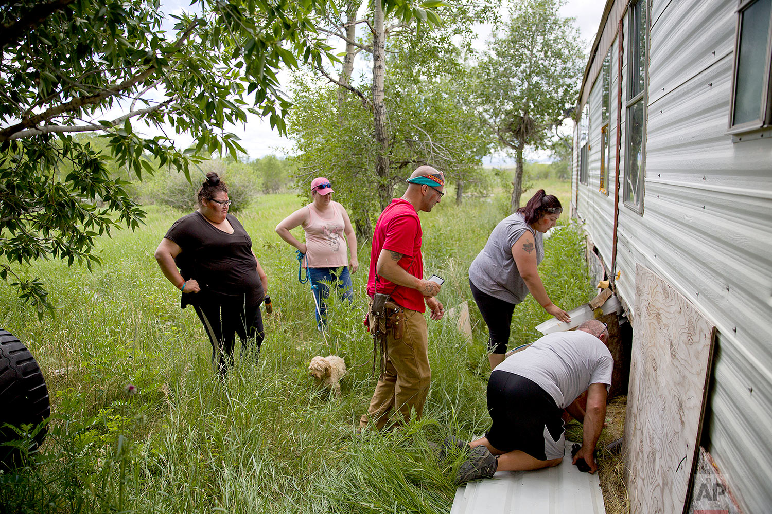 Kimberly Loring, from left, Staci Salois, Randy Ortiz, Lissa Loring and George A. Hall, look for clues under a trailer during a search in Valier, Mont., for the Lorings' sister and cousin, Ashley HeavyRunner Loring,July 11, 2018. (AP Photo/David Goldman)