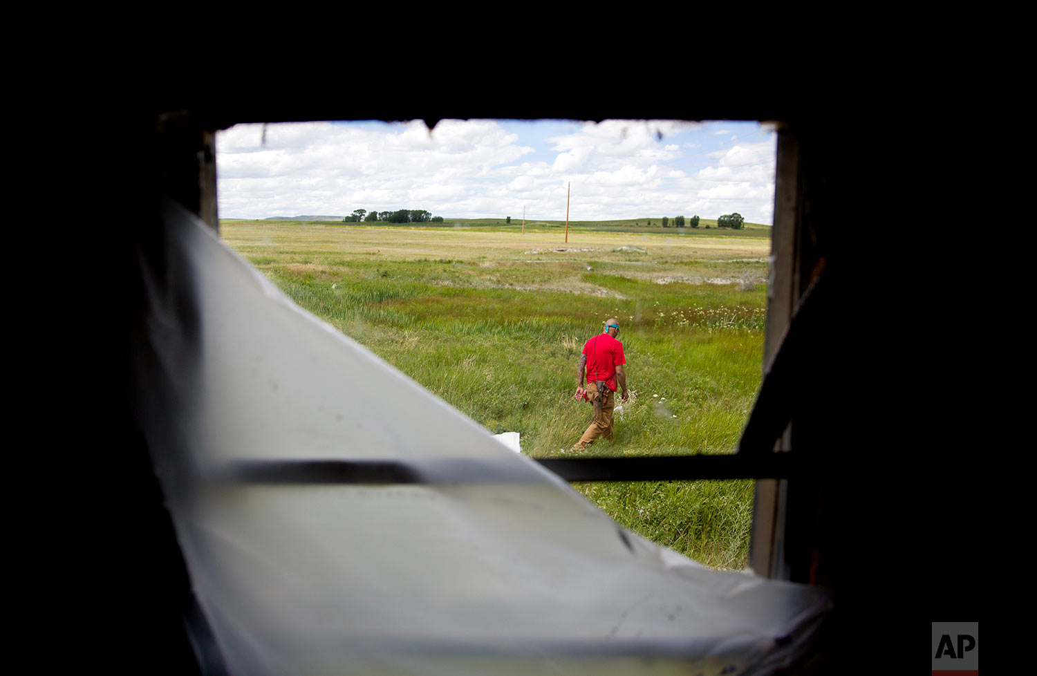 Randy Ortiz combs a field outside a trailer during a search for Ashley HeavyRunner Loring in Valier, Mont.,July 11, 2018.One of Ashley's cousins lived at the trailer, and there are reports it's among the last places she was seen. (AP Photo/David Goldman)