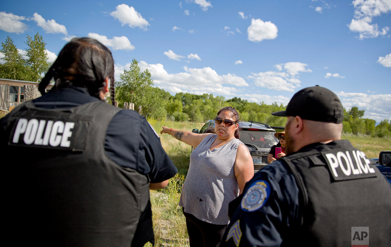 Lissa Loring points Blackfeet law enforcement officers to a trailer in Valier, Mont., where she believes clues have been found during a search for her cousin, Ashley HeavyRunner Loring, July 11, 2018. (AP Photo/David Goldman)