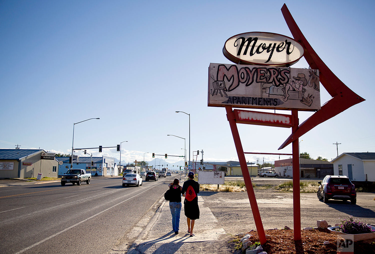 A couple walks through the main business district on the Blackfeet Indian Reservation in Browning, Mont., July 11, 2018. (AP Photo/David Goldman)