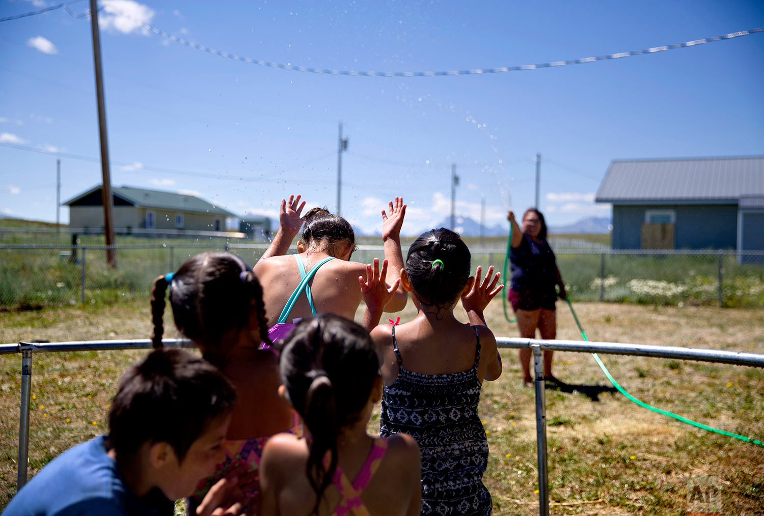 """Tyisha ArrowTop Knot, right, sprays her nieces and nephews with a garden hose while on the Blackfeet Indian Reservation in Browning, Mont., July 12, 2018. """"We've always been a cautious family,"""" she said of watching out for the children in light of recent disappearances of Native American women. """"The world is just getting worse.""""(AP Photo/David Goldman)"""