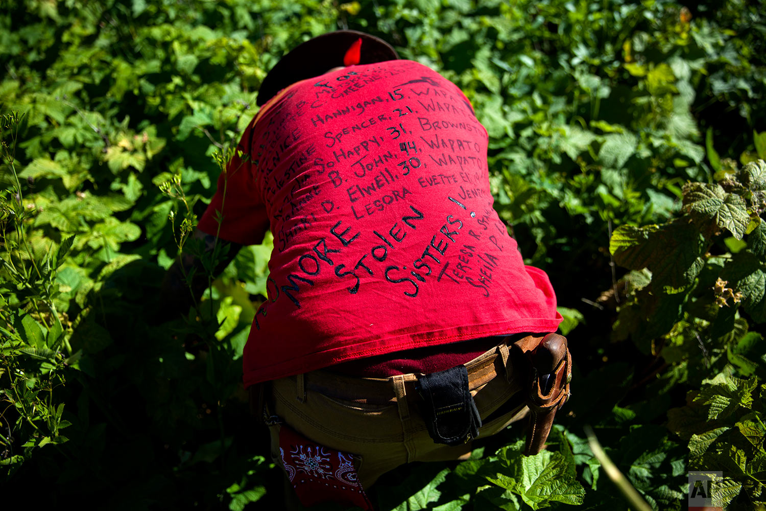 Randy Ortiz wears a shirt with the names of missing and murdered indigenous women as he searches for Ashley HeavyRunner Loring in the mountains of the Blackfeet Indian Reservation in Babb, Mont., July 12, 2018.(AP Photo/David Goldman)