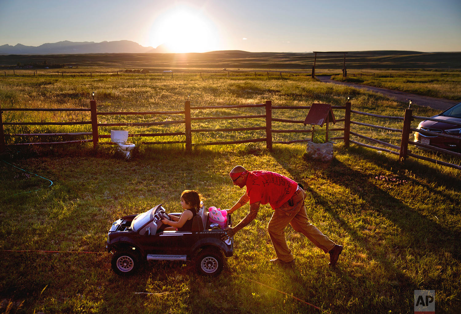 Randy Ortiz, right, pushes Ronnie Loring, 3, the cousin of Ashley HeavyRunner Loring, as they take a break from searching for her on the Blackfeet Indian Reservation in Browning, Mont., July 12, 2018. (AP Photo/David Goldman)
