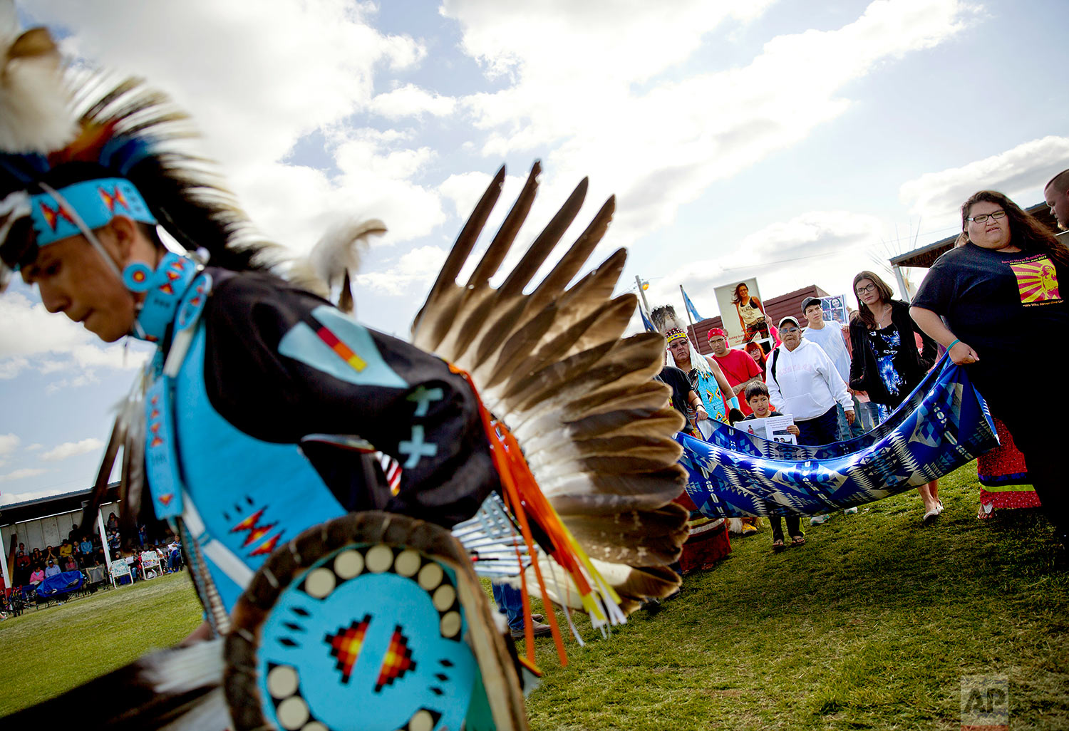 Friends and family members of Ashley HeavyRunner Loring hold a traditional blanket dance before the crowd at the North American Indian Days celebration to raise awareness and funds for her search on the Blackfeet Indian Reservation in Browning, Mont.,July 14, 2018. (AP Photo/David Goldman)