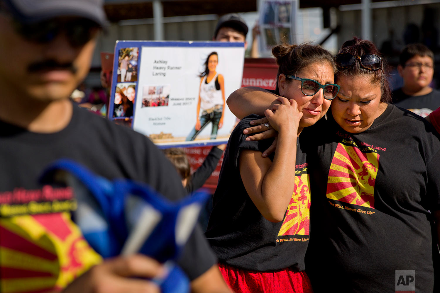 Jenna Loring, left, the aunt of Ashley HeavyRunner Loring, cries with her cousin, Lissa Loring, during a traditional blanket dance before the crowd at the North American Indian Days celebration on the Blackfeet Indian Reservation in Browning, Mont., July 14, 2018. (AP Photo/David Goldman)