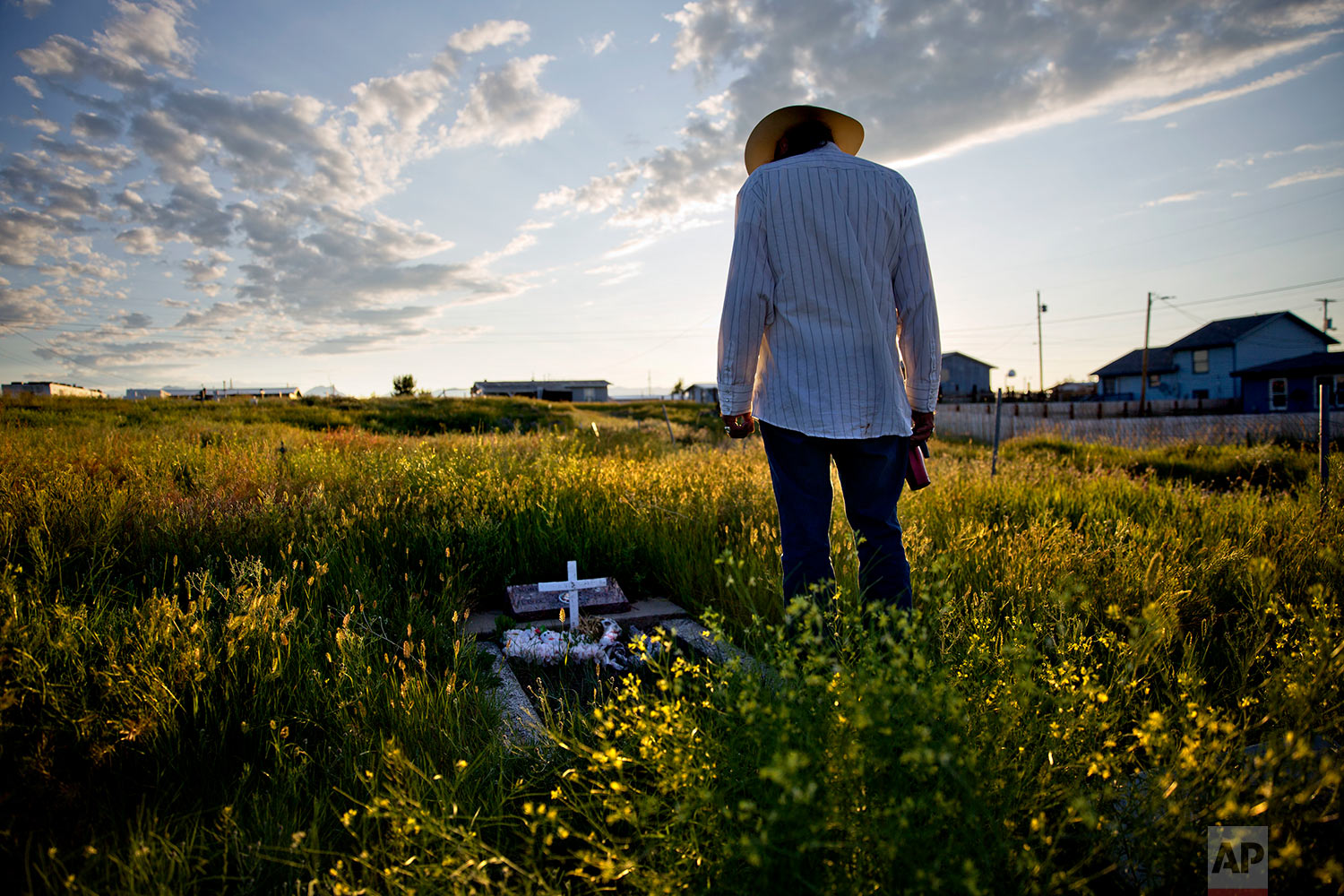 """Kenny Still Smoking stands over the tombstone of his 7-year-old daughter, Monica, as he visits her grave on the Blackfeet Indian Reservation in Browning, Mont.,July 14, 2018. """"I talk to her, let her know I'm doing OK, that I'm still kicking,"""" he said. """"I think about her all the time.""""(AP Photo/David Goldman)"""