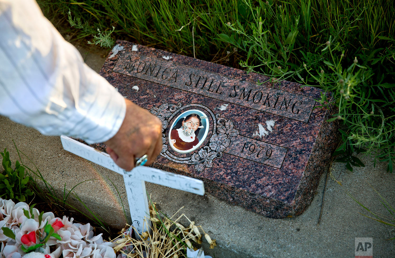 Kenny Still Smoking stands over the tombstone of his 7-year-old daughter, Monica, as he visits her grave on the Blackfeet Indian Reservation in Browning, Mont.,July 14, 2018. AP Photo/David Goldman)